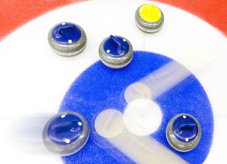 curling: Blue stone precicely delivered, to bounce away two yellow stones from the house of a curling rink - the winning shot. Stock Photo