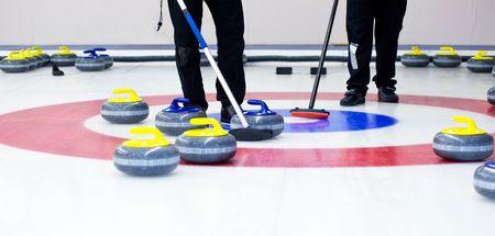 determining: Dos jugadores con escobas en el hielo, determinar la estrategia durante un juego de curling Foto de archivo