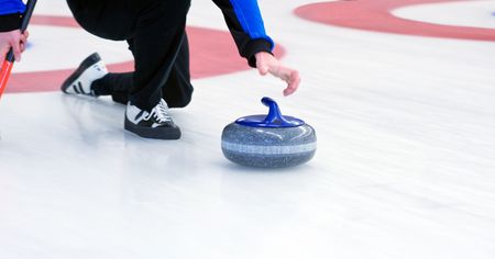 curling: Curling player delivering a stone on a curling rink, sliding over the ice