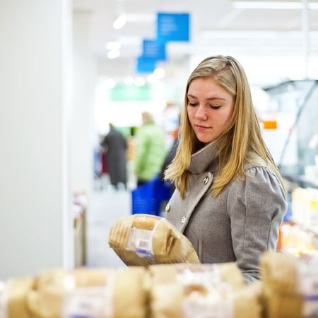 Young woman examining a loaf of bread at a supermarkets' bakery, with a shallow depth of field Stock Photo - 6402347