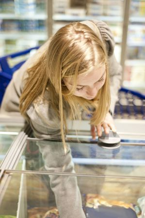 Young woman reaching in a freezer of the frosen food section of a supermarket, shallow Depth of field, focus on the eyelids photo