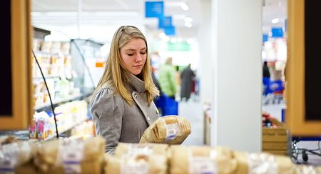 deliberation: Young woman examining a loaf of bread at a supermarkets bakery Stock Photo