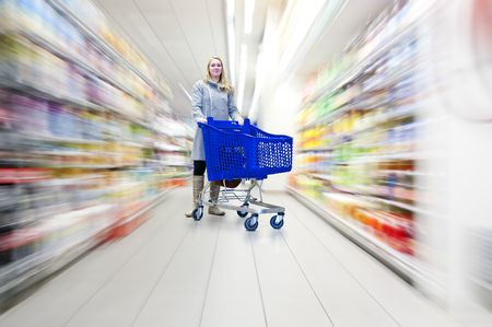 supermarket shelves: Confident woman with her shopping cart in a supermarket, doing groceries - what to choose