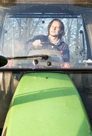 Farm hand behind the wheel of a tractor, seen through thge windscreen Stock Photo - 6481546