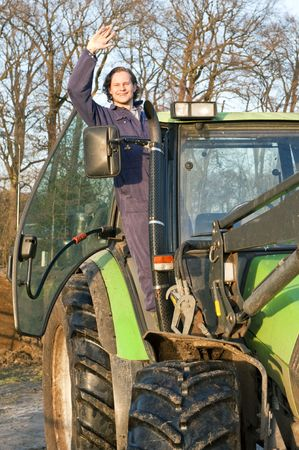 A happy farm hand standing in the door opening of a big tractor, waving at the camera Stock Photo - 6481527