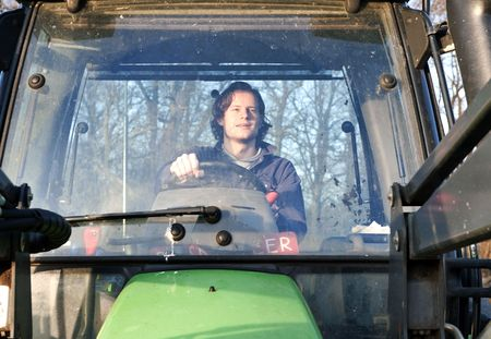 Farm hand behind the wheel of a tractor, seen through the windscreen photo