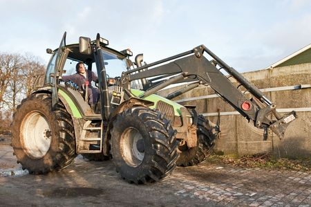 Farm hand behind the wheel of a tractor, closing the door Stock Photo - 6481528