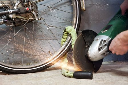 Thief opening the lock of a bicycle with a portable grinding machine photo
