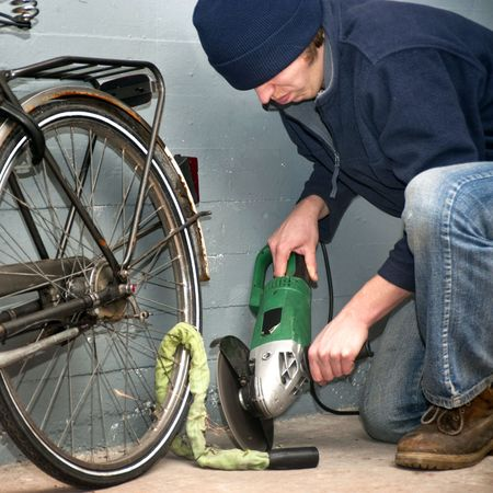 petty theft: Criminal grinding through the lock of a stolen bicycle Stock Photo