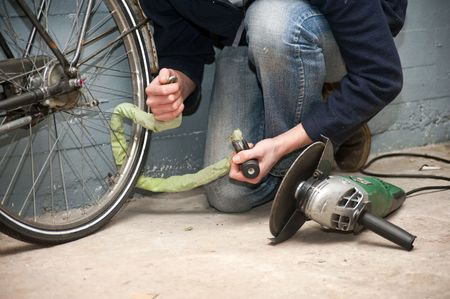petty theft: Thief opening the lock of a bicycle with a portable grinding machine Stock Photo