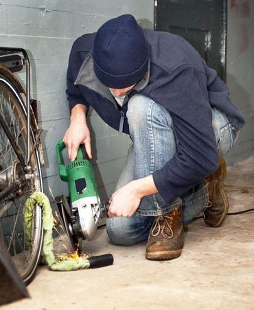 petty theft: Bicycle thief busy breaking the lock with a portable grinding machine