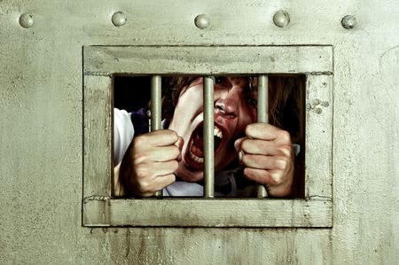 prisoner man: Cross-processed image of a man going insane, grabbing the bars of his jail cell, looking rabit and screaming uncontrollably Stock Photo