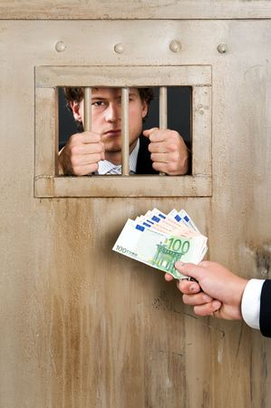 Incarcerated white collar criminal, clutching the bars of a cell door, with a hand holding a substantial amount of cash as bribe photo