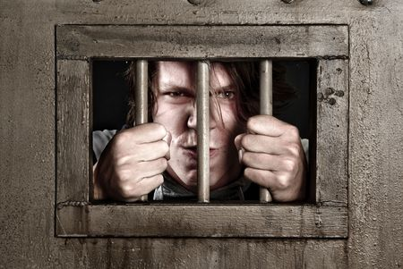 lonelyness: A CP of a man in prison holding the bars of his cell door. Stock Photo