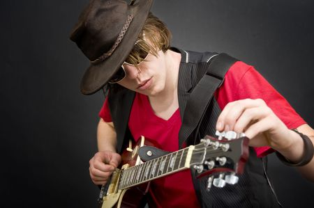 pegheads: A cool looking guitar player tuning his instrument Stock Photo