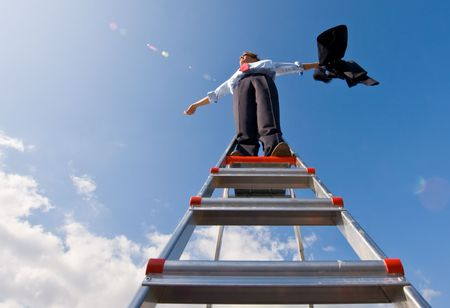 entrepreneurship: A businessman spreading his arms in the wind, standing on top of a ladder, whilest holding his jacket.