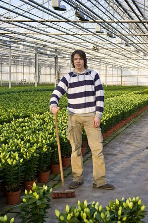 blind people: A man posing with a broom in his hand in a huge glasshouse