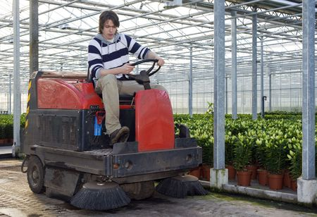 A man on an industrial cleaning machine, cleaning the concrete floor of a glasshouse Stock Photo - 6484158
