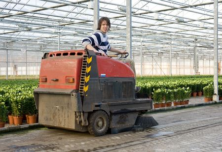 A man, driving an industrial cleaning cart, working hiw way through the concrete flooring of a huge glasshouse Stock Photo - 6484359