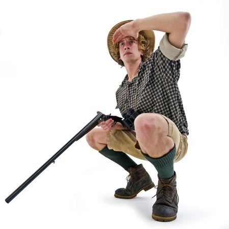 охотник: A crouching hunter, with a gun in his hand, searching for his prey Фото со стока