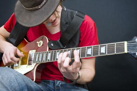 virtuoso: A guitarist improvising with a plectrum in his mouth