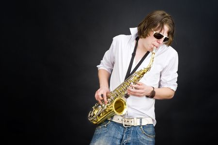 jamming: A musician in a white shirt jamming away on a saxophone, improvising Stock Photo