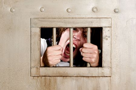 insane insanity: Man in prison going insane, grabbing the bars of his jail cell, looking rabit and screaming uncontrollably Stock Photo