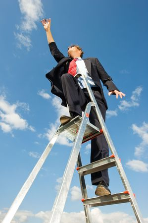 A businessman on a ladder reaching for the sky as if the limit is beyond the sky. photo