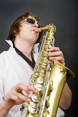 open collar: A man in a white shirt and open collar passionately playing the saxophone