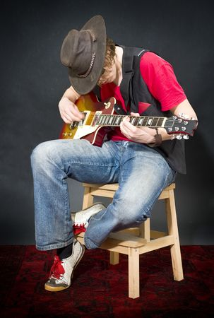 pegheads: A musician wearing an old, leather hat, playing on his guitar whilst sitting on a stool