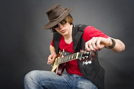 pegheads: A musician wearing an old leather hat tuning his guitar Stock Photo