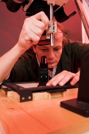 enlarger: Photographger in a darkroom finetuning the focus of the enlarger, peering through a focus scope Stock Photo