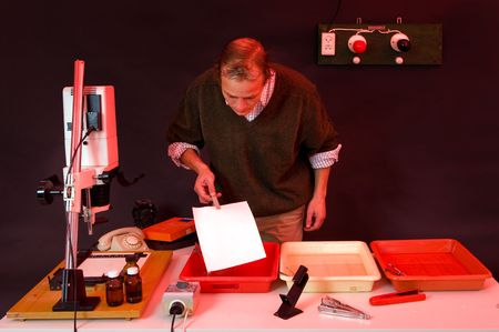 enlarger: Photographer printing photos in a dark room, putting the freshly exposed sheet in the develop bath