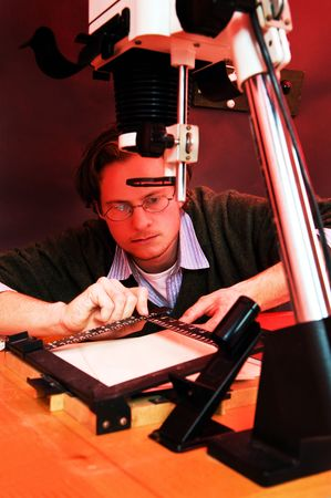 enlarger: Photographer in a dark room placing a sheet of paper under an enlarger and adjusting the easel Stock Photo