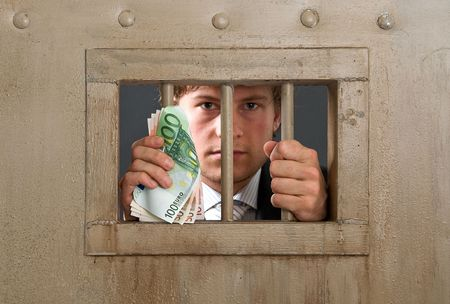 White collar criminal in jail for fraud, holding the bars with a substantial amount of cash in his hands photo