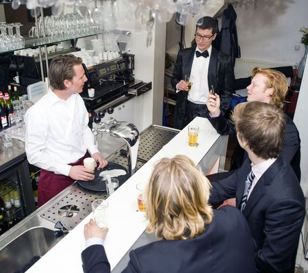 barman: Four customers around a bar, being served by a barman
