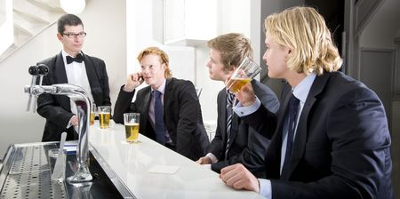 Four customers around a bar, being served by a barman photo