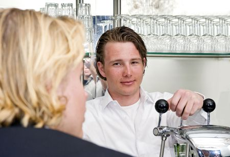 a proud bartender looking at a talking customer while leaning on the handles of his bar Stock Photo - 6484990