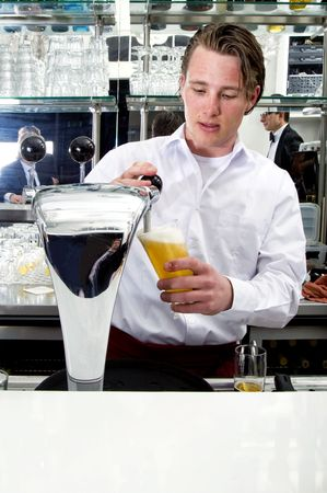beer pump: a bartender tapping a beer from his beer pump with customers in the reflection of the mirror Stock Photo