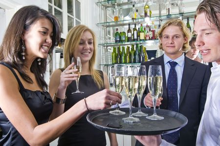a waiter serving glasses of champagne on a tray in a restaurant Stock Photo - 6484399