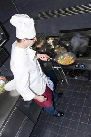 A chef and his sous-chef working in a kitchen photo