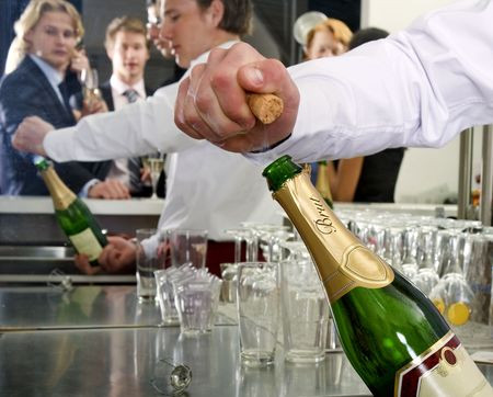 A bar man opening a bottle of champagne behind a bar, with several people reflected in the mirror behind him photo