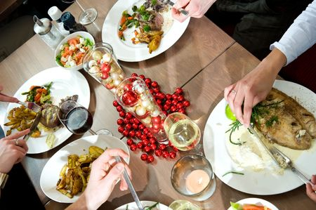 Meals being eaten on a restaurant table decorated for christmas photo