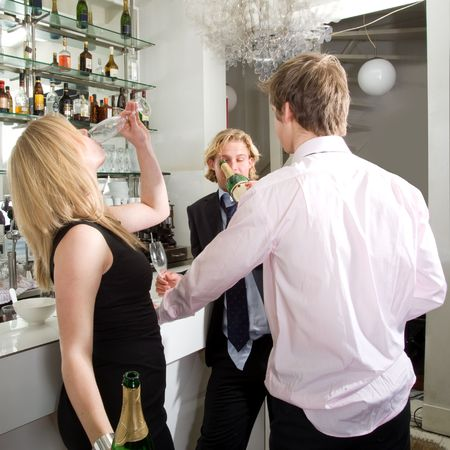 Three drunken people at the bar, guzzling the last few drops of champagne from a bottle photo