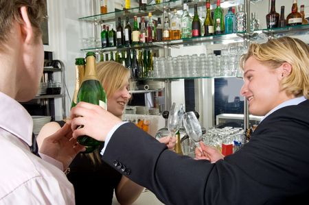 Three drunk people at the bar, drinking champagne photo