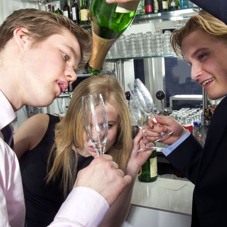 Three drunken people trying to sqeeze the last drop from a bottle of campagne photo