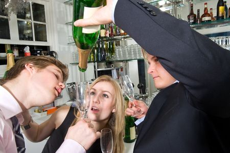 disoriented: three young, drunken adults taking the last drop of champagne at a bar