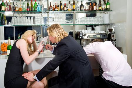 drunks: three young adults sitting at a bar; one sleeping, the others flirting with each other  Stock Photo