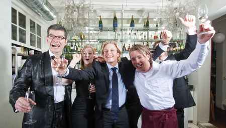 exuberant: Group of friends cheering in a restaurant bar Stock Photo