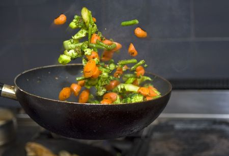 frying: Vegetables flying mid air, being flipped from a frying pan